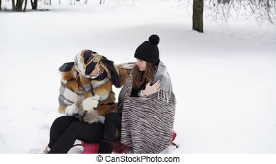 Two girls covered in warm plaid sitting in winter park