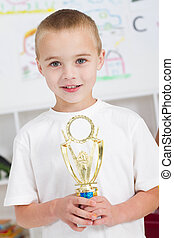 preschool boy holding a trophy