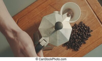Pouring coffe into white cup from the coffee geyser -...