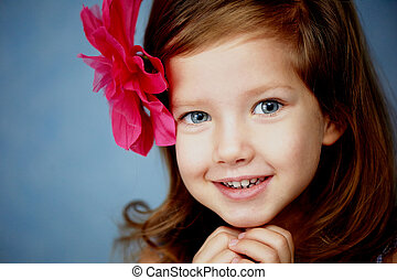 beautiful little girl with the red barrette in the shape of...