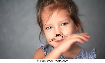 Baby 3 years with face painting of a cat, meowing and...