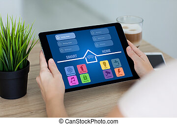 woman holding tablet with app smart home screen in room -...