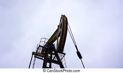 Small private yellow derrick pumps oil.