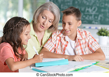 granny with grandchildren doing homework, at home together