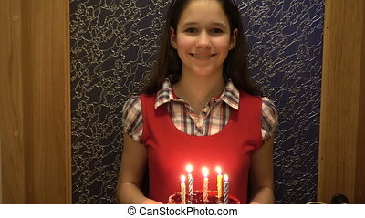 Girl carries the birthday cake with candles