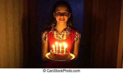 Girl carries the birthday cake with candles from the darkness