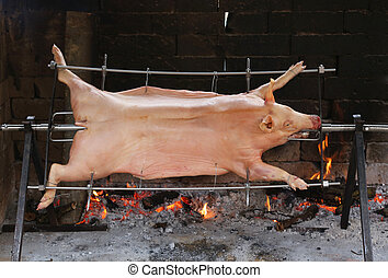 great stuck pig that cooks slowly on steel spit in the gigantic