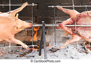 two pigs that cook slowly on steel spit in the fireplace