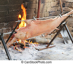 pig on the spit and slowly cooked on the large fireplace...