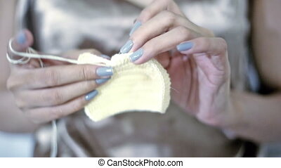 Soft focused young girl's hands crocheting with yellow yarn