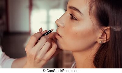 Makeup artist paints her lips a beautiful young brunette.