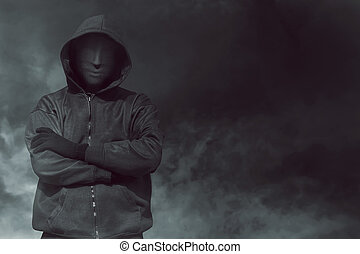 Hooded man with mask standing alone in the empty dark room