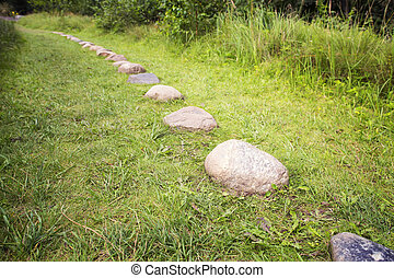 Path from cobble-stones on green herbs a background - Way...