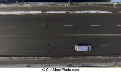 Aerial - Cars driving on two-lane road through a snowy...