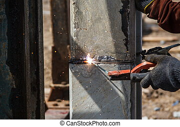 Welder worker in protective mask hand holding arc welding torch working on metal construction