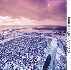 Aerial view of Suburban town next to a river and fields at sunset in winter.