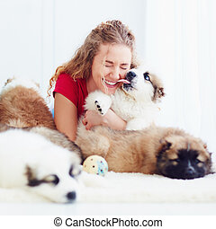 funny moment of cute puppy licking laughing girl