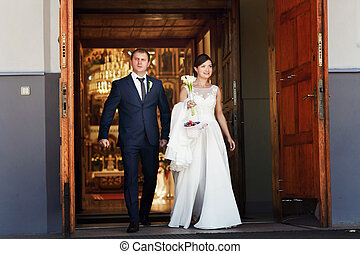 Stylish newlyweds   walk out of the cathedral