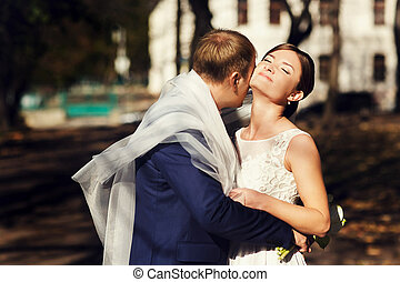 Groom hugs a bride being hidden under a veil