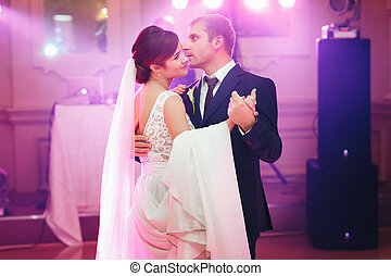 Groom holds bride's hand during their first dance