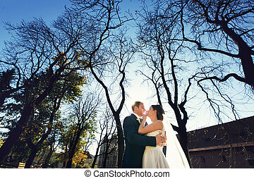 A view from below on a weding couple standing in the autumn...