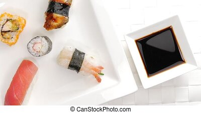 Pick and dip shrimp sushi in soy sauce - Male hand picking a...