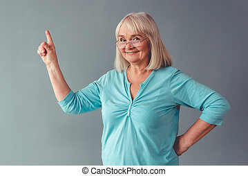 Beautiful mature woman in eyeglasses is pointing away,...