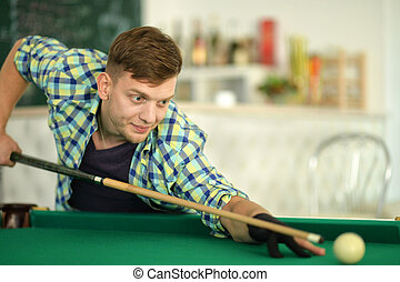 young man playing billiard - Portrait of a young man playing...