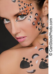 portrait of beautiful woman with face art on dark background