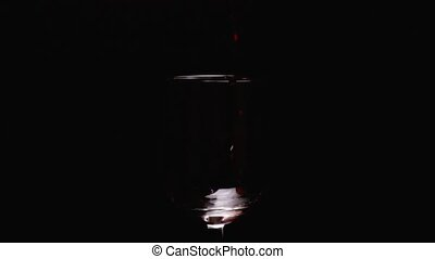 Slow mo splashes of red wine in glass on black background