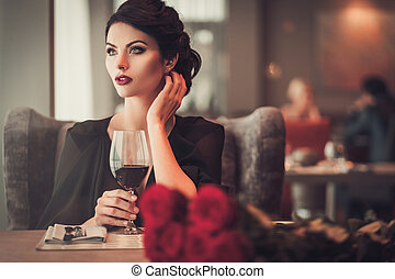 Elegant brunette lady with glass of red wine in restaurant