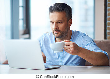 Handsome man with cup of coffee using laptop at home.