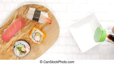 Pouring soy sauce in dish beside sushi - Pouring soy sauce...
