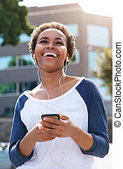 beautiful young black woman laughing with earphones and cellphone