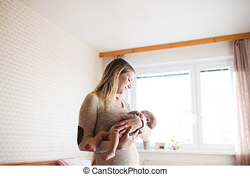 Beautiful young mother holding baby son in her arms -...
