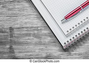Blank copybooks biro pen on wood board office concept.