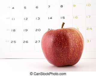 An apple a day - Close-up of an apple with a calendar on the...