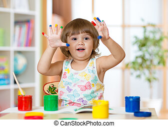 cute cheerful kid girl showing her fingers painted in bright...