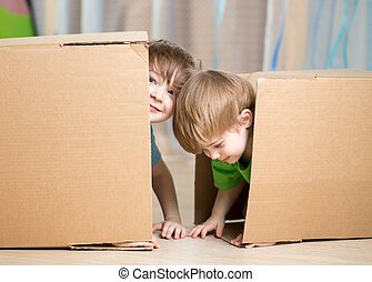 Child and toddler boys playing in cardboard boxes