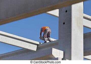 Construction worker assembling concrete truss - Construction...