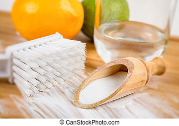 Baking soda in a wooden spoon next to a brush, two lemons...
