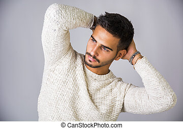 Handsome young man wearing white sweater