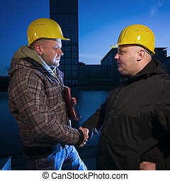 handshake with helmets - Torso view in soffit of two men...