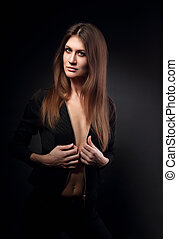 Sexy slim model posing in black jacket with long straight hair style on dark background. Fashion portrait