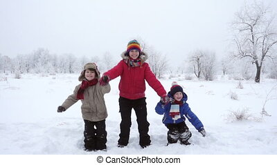 Three kids jumping together on winter landscape, slow motion...