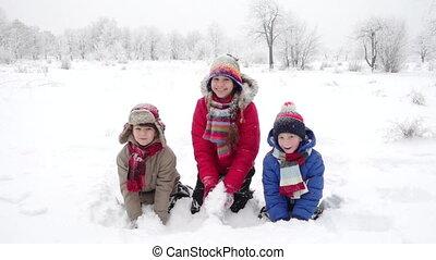 Three happy kids throwing snow on winter landscape, slow...
