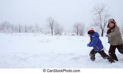 Three kids running together on winter landscape, slow motion...