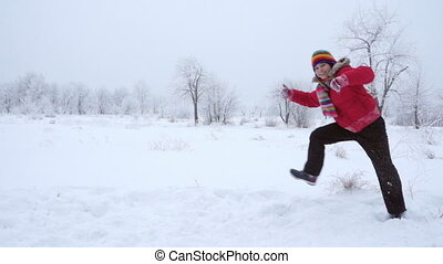 Girl running and jumping on winter landscape, slow motion
