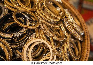 Set of traditional golden indian bracelets on a market - Set...
