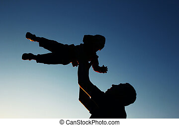 silhouette of father and son play on sunset - a silhouette...